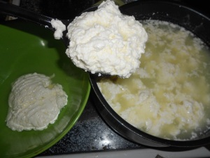 Removing curds from the pot with a slotted spoon